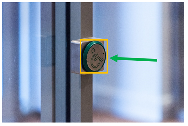External door open button on porch door frame. This image shows the external door open button for exiting onto the street if assistance with opening the door is required. Assistance can also be sought from staff or security staff.This image also shows the button highlighted by a yellow box and a green arrow pointing to the yellow box.